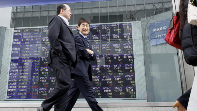 People walk past the stock prices displayed on an electronic board of a securities firm in Tokyo, Wednesday, March 4, 2015. Asian stock markets were mostly lower Wednesday after Wall Street declined and investors looked ahead to U.S. economic data and China's announcement of its annual growth target. (AP Photo/Shuji Kajiyama)