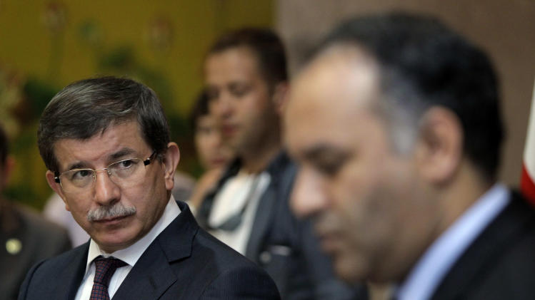 Turkish Foreign Minister Ahmet Davutoglu, left, speaks to Vice-Chairman of the Executive Board of the Libyan National Transitional Congress Ali al-Issawi, right, during a news conference after their meeting in the rebel-held Benghazi, Libya, Sunday, July 3, 2011.  (AP Photo/Sergey Ponomarev)