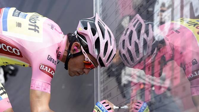 Tinkoff-Saxo rider Alberto Contador of Spain signs a board before the 236 km 98th Giro d'Italia cycling race from Gravellona Toce to Cervinia