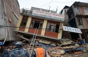 Nepalese rescue personnel observe damaged buildings…