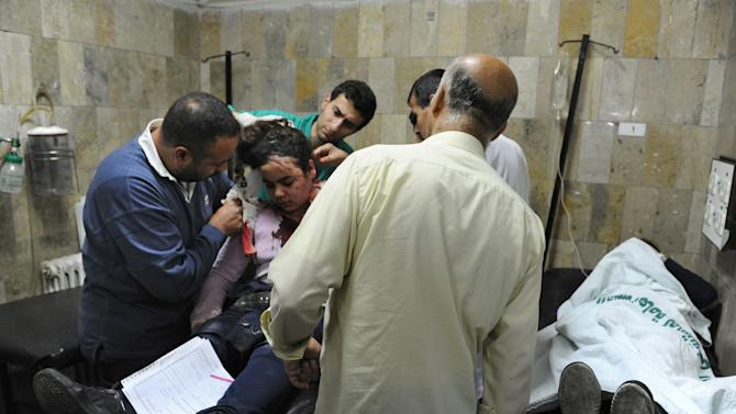 This photo released by the Syrian official news agency SANA, shows Syrian doctors treating an injured man who was wounded by a car bomb, in Damascus, Syria, Monday, April. 8, 2013. A car bomb rocked a busy residential and commercial district in central Damascus on Monday, killing more than a dozen with many more injured and sending a huge cloud of black smoke billowing over the capital's skyline, Syrian state-run media said. (AP Photo/SANA)