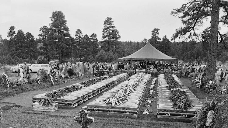 FILE - In this July 9, 1956 file photo, nearly four hundred relatives and friends of the 70 people who died in the crash of a TWA Super-Constellation over the Grand Canyon June 30, 1956 attend a mass funeral service in Flagstaff, Ariz. Sixty-seven caskets, three of the identified dead having been returned at relatives request to their homes, will be lowered into a common grave. On Tuesday, July 8, 2014, the Grand Canyon National Park will mark the designation of the crash site as a National Historic Landmark in a ceremony overlooking the gorge where the wreckage was scattered over 1.5 square miles. (AP Photo/David F. Smith, File)