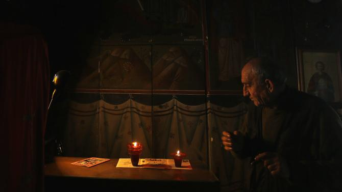 Evangelos, the caretaker of the Greek Orthodox church of Saint George, prepares vigil oil lamps inside the 19th century church atop the Lycabettus hill overlooking Athens