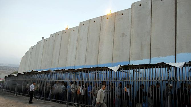 File photo shows Palestinians waiting to cross into Jerusalem next to Israel's controversial barrier at an Israeli checkpoint in Bethlehem