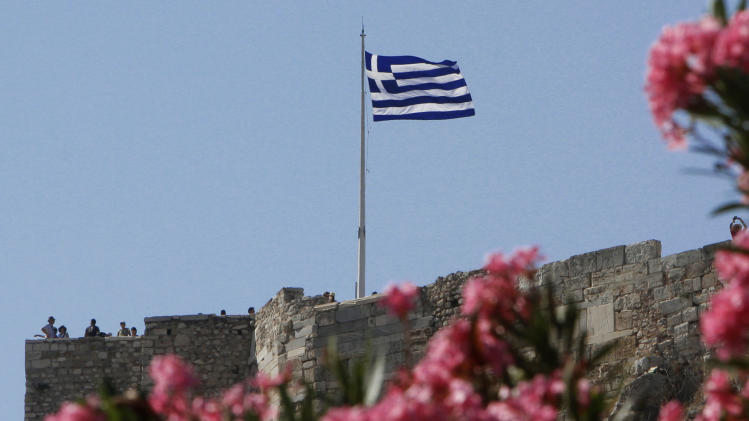 Tourists stand next a Greek flag at the Acropolis hill in central Athens, on Friday, June 15, 2012. Tourism and shipping are among the pillars Greek economy. Both are under strain amid speculation about whether Greece will have to abandon the euro in a chaotic and possibly economically debilitating exit. (AP Photo/Petros Karadjias)