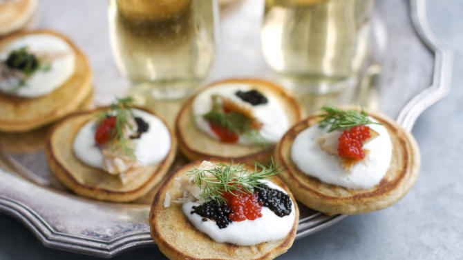 This Jan. 28, 2013 photo shows blini with smoked trout, caviar and horseradish cream served on a platter in Concord, N.H. These elegant hors d'oeuvres are perfect for an Oscar night viewing party. (AP Photo/Matthew Mead)