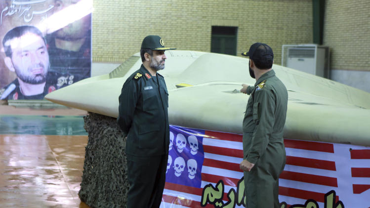 This photo released on Thursday, Dec. 8, 2011, by the Iranian Revolutionary Guards, claims to show the chief of the aerospace division of Iran's Revolutionary Guards, Gen. Amir Ali Hajizadeh, left, listening to an unidentified colonel as he points to US RQ-170 Sentinel drone which Tehran says its forces downed earlier this week. An anti-US banner is placed under the drone. The banner at left shows Gen. Hasan Tehrani Moghaddam, a senior Iranian Revolutionary Guard commander who was killed in an explosion at an ammunition depot last month. (AP Photo/Sepahnews) EDS NOTE: THE ASSOCIATED PRESS HAS NO WAY OF INDEPENDENTLY VERIFYING THE CONTENT, LOCATION OR DATE OF THIS IMAGE.