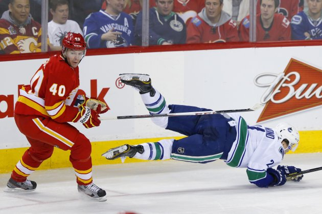 Vancouver Canucks' Raymond is sent flying by Calgary Flames' Tanguay during their NHL hockey game in Calgary