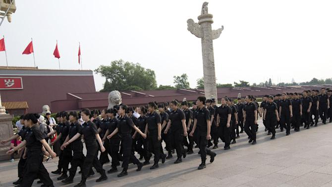 Female and male security guards march in front of Tiananmen Gate in Beijing Saturday, May 31, 2014. A quarter century after the Tiananmen Square pro-democracy movement's suppression, China's communist authorities oversee a raft of measures for muzzling dissent and preventing protests. They range from the sophisticated - extensive monitoring of online debate and control over media - to the relatively simple - routine harassment of government critics and maintenance of a massive domestic security force. (AP Photo/Alexander F. Yuan)