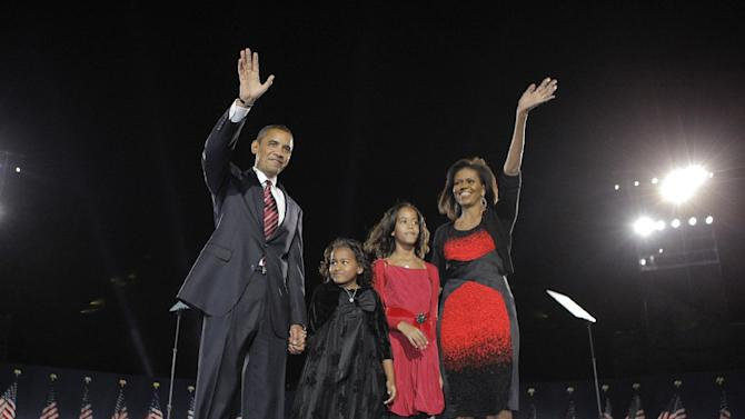 FILE - This Nov. 4, 2008 file photo shows President-elect Barack Obama, left, his wife Michelle Obama, right, and two daughters, Sasha, 7, and Malia, 10, second from right, as they wave at the election night rally in Chicago. Michelle Obama has proven her fashion savvy time and time again since she was introduced to the country as first lady on Inauguration Day 2009. In the past four years she has adeptly walked the line between directional fashionista and everywoman. (AP Photo/Jae C. Hong, file)