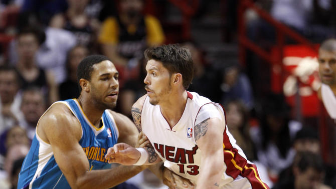 Miami Heat's Mike Miller (13) drives around New Orleans Hornets'  Xavier Henry, left, in the second half of an NBA basketball game in Miami, Monday, Jan. 30, 2012. Miami won 109-95. (AP Photo/Alan Diaz)