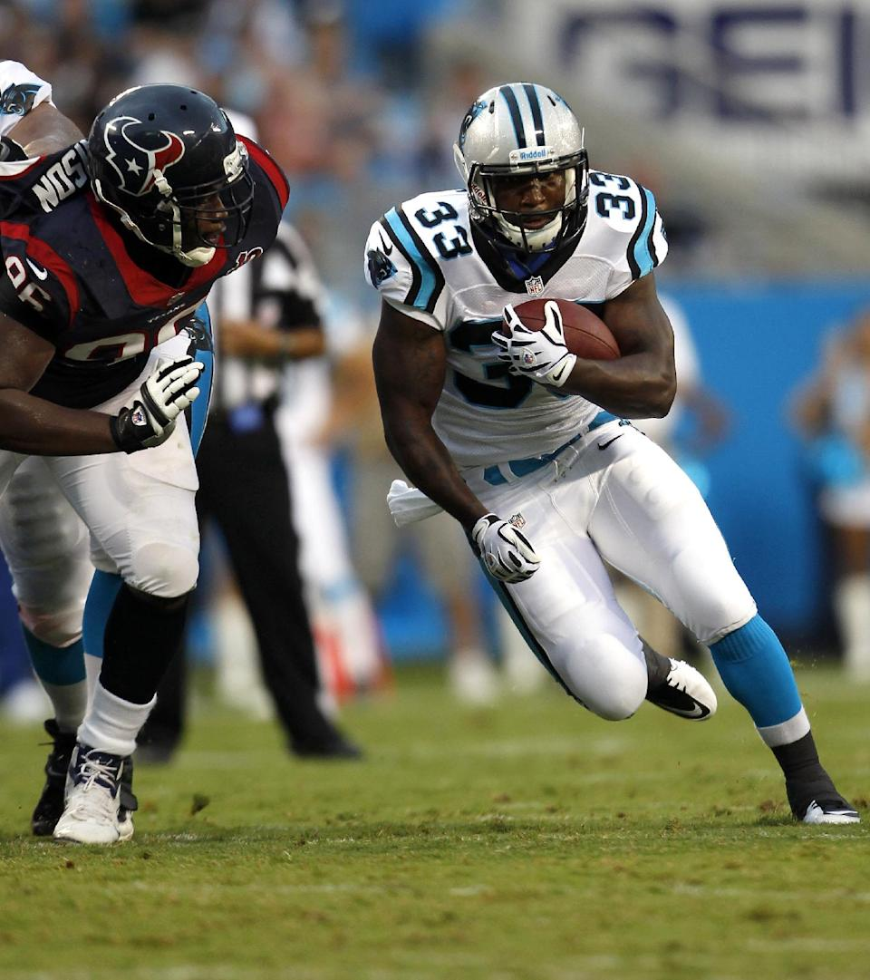 Carolina Panthers' Tauren Poole (33) runs the ball as Houston Texans' Tim Jamison chases during the first half of an NFL preseason football game in Charlotte, N.C., Saturday, Aug. 11, 2012. (AP Photo/Bob Leverone)