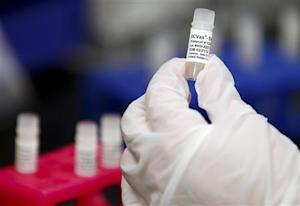 A manufacturing associate holds a vial with a DCVax-L label in a Northwest Biotherapeutics laboratory in Memphis