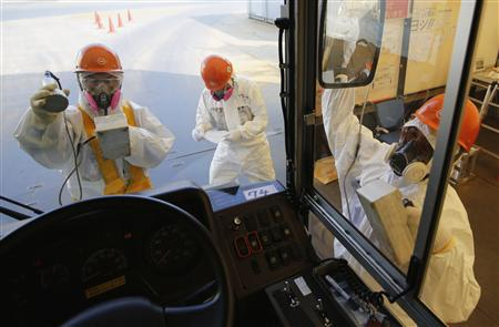 Workers carry out radiation screening on bus for media tour at TEPCO's tsunami-crippled Fukushima Daiichi nuclear power plant in Fukushima prefecture