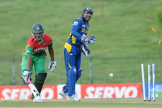Bangladeshi cricketer Tamim Iqbal (L) avoids a run out as wicketkeeper Kumar Sangakkara looks on during the opening one-day international (ODI) match between Sri Lanka and Bangladesh at The Suriyawewa