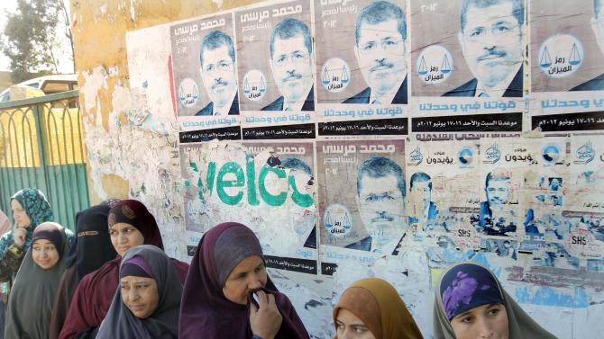 """Egyptian women line up to vote under posters showing Egyptian president Mohammed Morsi and Arabic reading, """"our strength in our unity,"""" in the second round of a referendum on a disputed constitution drafted by Islamist supporters of Morsi in Giza, Egypt, Saturday, Dec. 22, 2012.  (AP Photo/Amr Nabil)"""