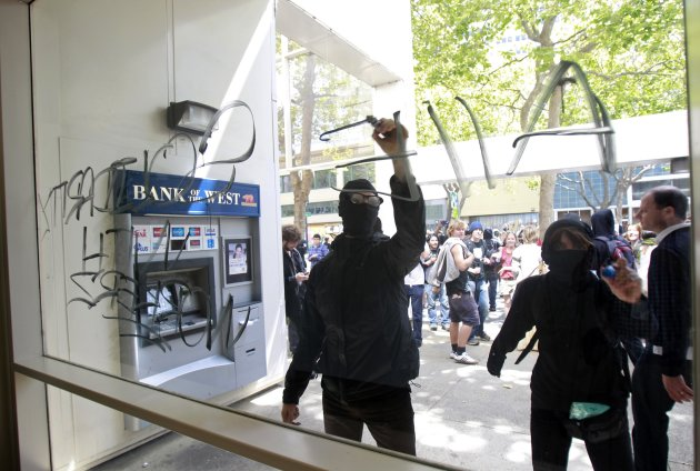 Occupy demonstrators write slogans on a window of a Bank of The West building during May Day protests in Oakland