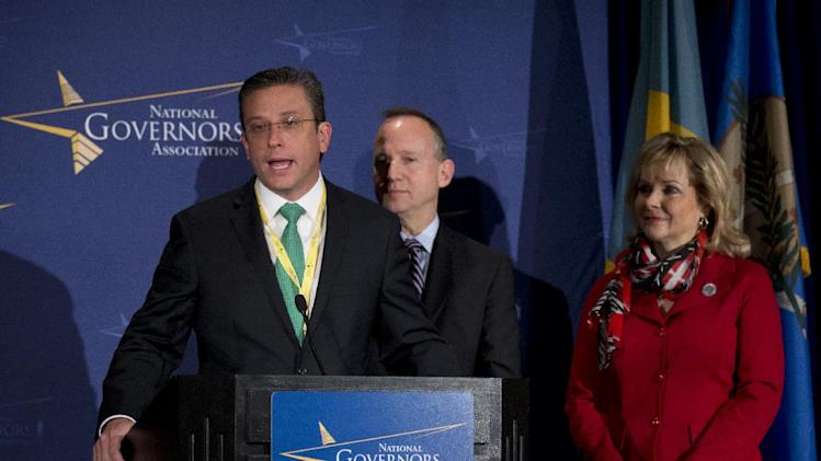 Governor of Puerto Rico Alejandro García Padilla, from left, seen with National Governors Association Chairman Gov. Jack Markell of Delaware and Vice Chairman Gov. Mary Fallin of Oklahoma, right, speaks during a news conference at the NGA Winter Meeting in Washington, Saturday, Feb. 23, 2013.  The nation's governors say their states are threatened if the automatic, across-the-board budget cuts, known as the sequester, take effect March 1.  (AP Photo/Manuel Balce Ceneta)