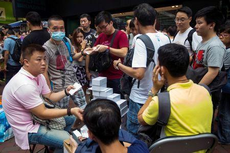 Traders buy the newly-released Apple iPhone 6 and iPhone 6 Plus smart phones from people who bought the phones earlier from the Apple store, at Hong Kong's Mongkok shopping district