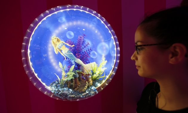 """A staff poses for the photographer next Mattel's Barbie dolls are pictured inside a life-size so-called """"Barbie Dreamhouse"""" during a media tour in Berlin"""