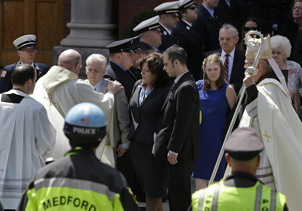 A priest comforts family members of Boston Marathon bomb victim Krystle Campbell after her funeral at St. Joseph's Church in Medford, Mass. Monday, April 22, 2013. At center is her mother, Patty Campbell, and her brother, Billy. At far right is Boston Cardinal Sean O'Malley. (AP Photo/Elise Amendola)