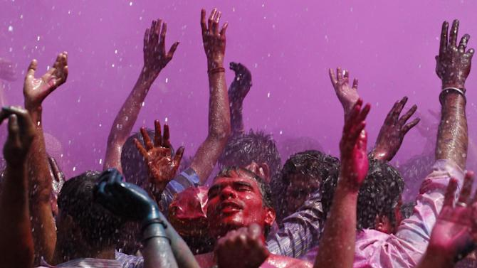 Indians, their faces smeared with color and glitter, dance as water is sprinkled on them during Holi celebrations in Allahabad, India, Wednesday, March 27, 2013. Holi, the Hindu festival of colors that also marks the advent of spring, is being celebrated across the country Wednesday. (AP Photo/ Rajesh Kumar Singh)
