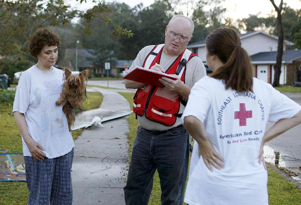 Diane Pierce, 69, left, talks with Red Cross damage assessors Mike and Anna Bradford, after strong winds from a suspected tornado damaged her home in the Lafayette Woods subdivision Wednesday, Nov. 16, 2011 in Houma, La.   No one was injured. (AP Photo/The Houma Courier, Julia Rendleman)