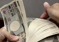 A teller counts 10,000 yen banknotes in Tokyo. The Bank of Japan has followed its US and European counterparts in announcing extra bond buying to take its total monetary easing effort past $1 trillion as it seeks to revitalise the economy