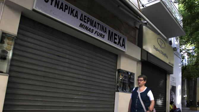 A woman walks by closed shops at the main commercial Athens Ermou street on Tuesday Nov. 6, 2012. Greece's unions are holding their third general strike in six weeks to press dissenters in the country's troubled coalition government not to back a major new austerity program that will doom Greeks to further hardship in a sixth year of recession. (AP Photo/Nikolas Giakoumidis)