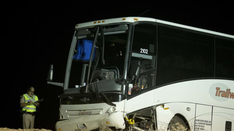 An Arizona Highway Patrol officer examines the exterior of a tour bus that careened off the highway and crashed off northbound highway 93, Friday, Oct. 19, 2012, near Willow Beach, Ariz. The crash killed the driver and left at least four passengers with serious injuries. About 45 other passengers were less seriously hurt and not all of them required hospital treatment, the Arizona Highway Patrol said. (AP Photo/Julie Jacobson)