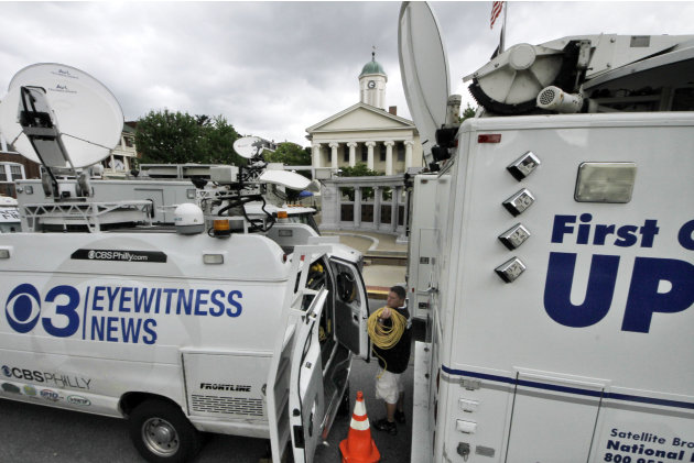Television satellite trucks set up outside the Centre County Courthouse in Bellefonte, Pa., Monday, June 4, 2012, in preparation for the start of the child sexual abuse trial of former Penn State assi