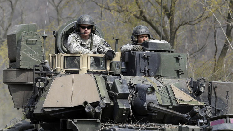 U.S. Army soldiers ride an armored vehicle during their military exercise near the border village of Panmunjom, that separates the two Koreas, in Paju, north of Seoul, South Korea, Wednesday, April 24, 2013. For weeks, North Korea has threatened to attack the U.S. and South Korea for holding joint military drills and for supporting U.N. sanctions. Washington and Seoul said they've seen no evidence that Pyongyang is actually preparing for a major conflict, though South Korean defense officials said the North appears prepared to test-fire a medium-range missile capable of reaching the American territory of Guam. (AP Photo/Lee Jin-man)