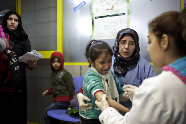 FILE - This Wednesday, Dec. 18, 2013 file photo shows a Syrian girl weeping after receiving the measles vaccine from UNICEF nurses Nadine Houjairi, second right, and Genivieve Bashalani, right, at the