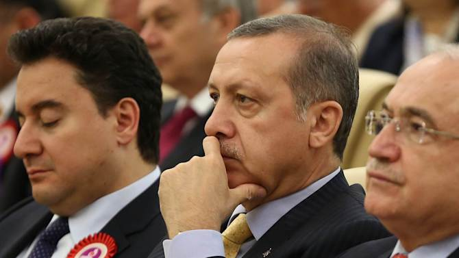 Turkey's Deputy Prime Minister Ali Babacan (L) and Prime Minister Recep Tayyip Erdogan (C)take part in a ceremony marking the 52nd anniversary of Turkey's Constitutional Court, on April 25, 2014 in Ankara