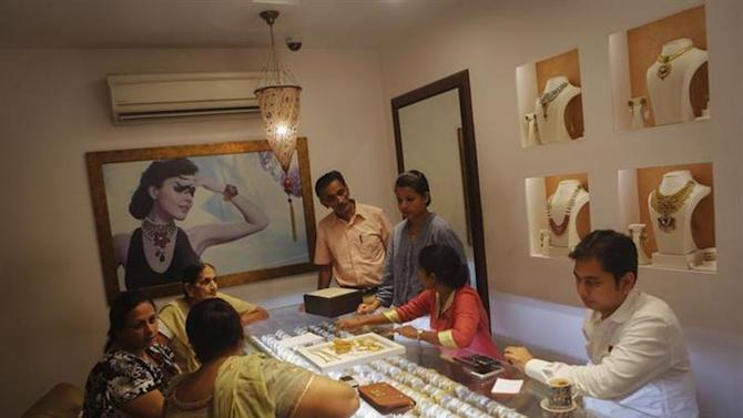 Customers shop inside a gold jewellery showroom in Mumbai August 30, 2013.