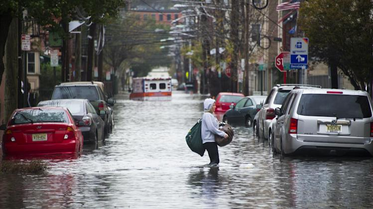 A resident walks through flood water and past a stalled ambulance in the aftermath of superstorm Sandy on Tuesday, Oct. 30, 2012 in Hoboken, NJ. (AP Photo/Charles Sykes)