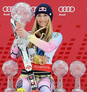 FILE - In this March 13, 2010, file photo, Lindsey Vonn of the United States, holds the Women's World Cup overall title trophy as she sits next to some of the World Cup discipline trophies she won during the season in Garmisch-Partenkirchen, Germany.Vonn was named the 2010 Female Athlete of the Year, Saturday, Dec. 18, 2010, chosen by member of The Associated Press.  (AP Photo/Giovanni Auletta, File)