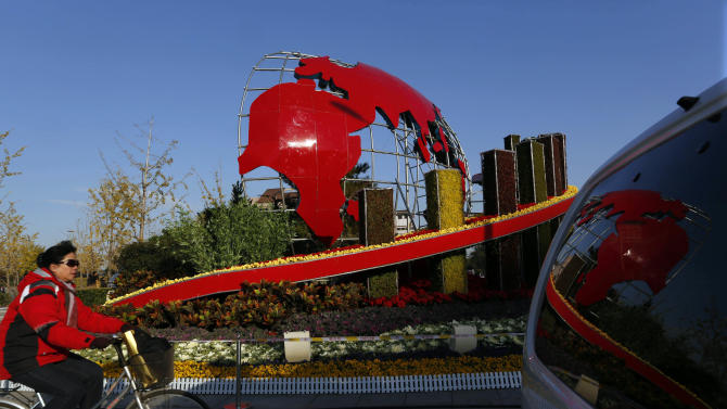 In this photo taken Monday, Nov. 12, 2012, a woman cycles by a floral decoration set up for the 18th Communist Party Congress held in Beijing, China. The Chinese capital's administrators havebedecked the city with towers of flower installations and othereye-catching landscaping decorations. State media say 20 million pots of flowers are being used in more than ahundredlocationsin preparation for the once-a-decade party congress to usher in a new generation ofleaders.  (AP Photo/Vincent Yu)