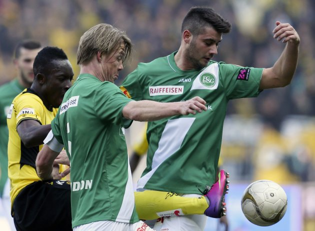 BSC Young Boys' Afum fights for the ball with FC St. Gallen's Montandon and Janjatovic during their Swiss Super League soccer match in Bern