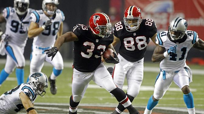 Atlanta Falcons running back Michael Turner (33) runs away from Carolina Panthers cornerback Captain Munnerlyn (41) and  free safety Haruki Nakamura (43) on a second half touchdown run in an NFL football game Sunday, Sept. 30, 2012, in Atlanta. (AP Photo/John Bazemore)