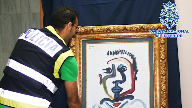 """In this photo released by the Spanish Police a police officer holds a forged Pablo Picasso oil painting in Sevilla, Spain, Saturday, July 7, 2012. The Interior Ministry says National Police have arrested four people for trying to sell a forged Pablo Picasso oil painting for up to 1.2 million euros ($1.5 million). The canvas, a counterfeit version of a 1964 work called """"The bust of Jeune Garcon"""" was accompanied by false authenticity documents bearing the signatures of Paloma, one of the Spanish painter's daughters, and a renowned French art expert. (AP Photo/Spanish Police)"""