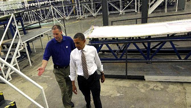 President Barack Obama, left, tours TPI Composites, a manufacturer of wind turbines blades, with plant manager Mark Parriott, Thursday, May 24, 2012 in Newton, Iowa. In Obama's second visit as president to Newton, a city of about 15,000 east of Des Moines, he argued for Congress to renew wind energy tax credits.(AP Photo/Pablo Martinez Monsivais)