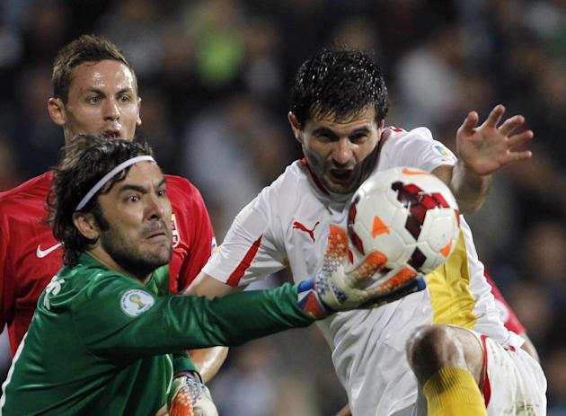 Serbia's goalkeeper Vladimir Stojkovic, left , challenges for the ball with Macedonia's Boban Grncarov during their World Cup 2014 Group A qualifying soccer match at the City Stadium in Jagodina, Serb