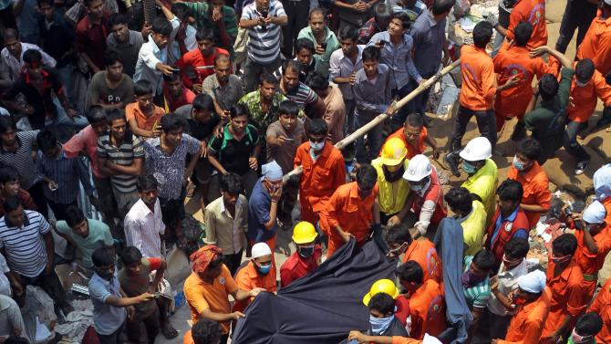 ADD EXPLANATION FOR USE OF A FABRIC - Bangladeshi people watch as rescuers use a piece of fabric to lower the body of a woman after she was discovered inside a building that collapsed Wednesday in Savar, near Dhaka, Bangladesh,Thursday, April 25, 2013. By Thursday, the death toll reached at least 194 people as rescuers continued to search for injured and missing, after a huge section of an eight-story building that housed several garment factories splintered into a pile of concrete on Wednesday. (AP Photo/A.M.Ahad)