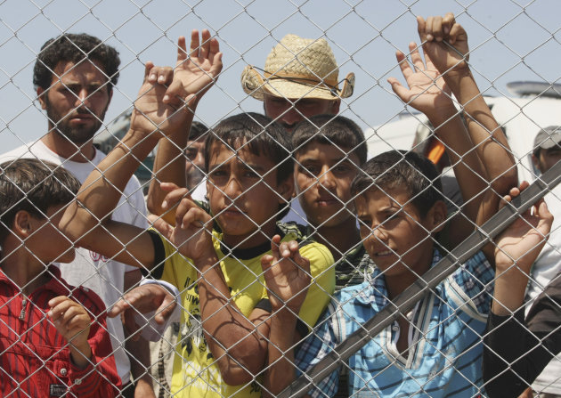 Refugee children look out from a fence, from inside a Syrian refugee camp just at the border in Turkey near Turkish village of Boynuyogun in Hatay province, Turkey, Friday, June 18, 2011, during a press tour organized by the Turkish authorities.(AP Photo/Burhan Ozbilici)