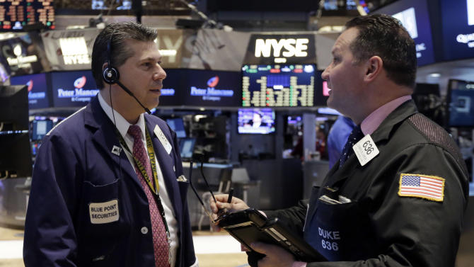 Traders William McInerney, left, and Edward Curran confer on the floor of the New York Stock Exchange, Friday, March 6, 2015. Stocks opened lower on Friday as another strong U.S. jobs report raised the likelihood that the Federal Reserve would start to raise interest rates later this year. (AP Photo/Richard Drew)