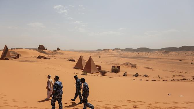 In this Thursday, April 16, 2015, photo, members of the Sudanese security forces guard the historic Meroe pyramids in al-Bagrawiya, 200 kilometers (125 miles) north of Khartoum, Sudan. The pyramids at Meroe are deserted despite being a UNESCO World Heritage site like those at Giza in Egypt. (AP Photo/Mosa'ab Elshamy)