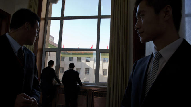 Chinese plain clothes security personnel watch over a corridor during the closing session of the 18th Communist Party Congress held at the Great Hall of the People in Beijing Wednesday, Nov. 14, 2012. (AP Photo/Ng Han Guan)