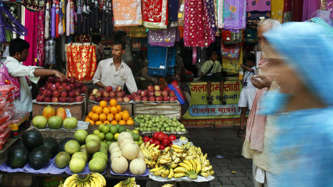 An Indian fruit vendor sells fruits to a customer in Mumbai, India, Monday, Sept. 17, 2012. India's central bank, Reserve Bank of India, on Monday cut the cash reserve ratio as it tries to kick-start flagging growth and welcomed government efforts to open Asia's third-largest economy to more foreign investment. The government's announcement allowing foreign companies in retail and raising the price of diesel has met with protests from opposition parties and some of the ruling Congress party's coalition partners. (AP Photo/Rafiq Maqbool)
