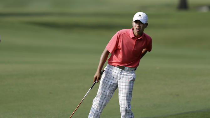 Amateur Guan Tianlang, 14, of China looks down the fairway before hitting on his approach to the 15th green during the first round of the Byron Nelson Championship golf tournament, Thursday, May 16, 2013, in Irving, Texas. (AP Photo/Tony Gutierrez)